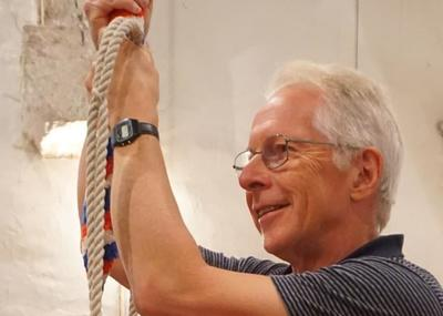A man holding a bell rope